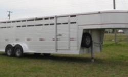 This 24' x 7' W W Trailer doesn't have Ribbons and Bows ! Just Quality materials and construction.  It has 7000# torsion axles , electric brakes, with ST 235x85R16 10 ply tires. 2 inside divide gates,half slide on back one,front curbside door, calf gate,