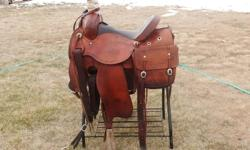 """15 1/2"""" Custom built association saddle. Padded Seat, Cheyenne Roll, Drop Plate Rigging. Basketweave tooling with a barbed wire border. Comes with matching basketweave breast collar and saddle bags. Very comfortable, good fitting saddle.  Can deliver as"""