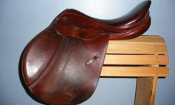 "Lovely close contact saddle in very good used condition. Soft, well cared for, some cosmetic wear at leg contact points of skirt. 17"" seat, 31cm tree. Mahogany in colour (reddish chestnut).  Comes with leathers, stirrups and girth.  Made in Switzerland."